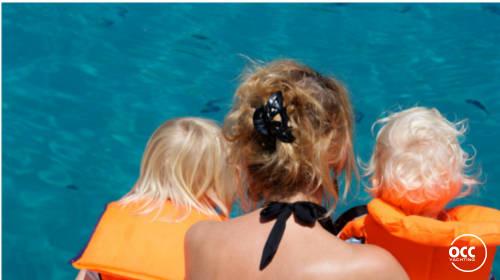 Moeder met kinderen bij het water